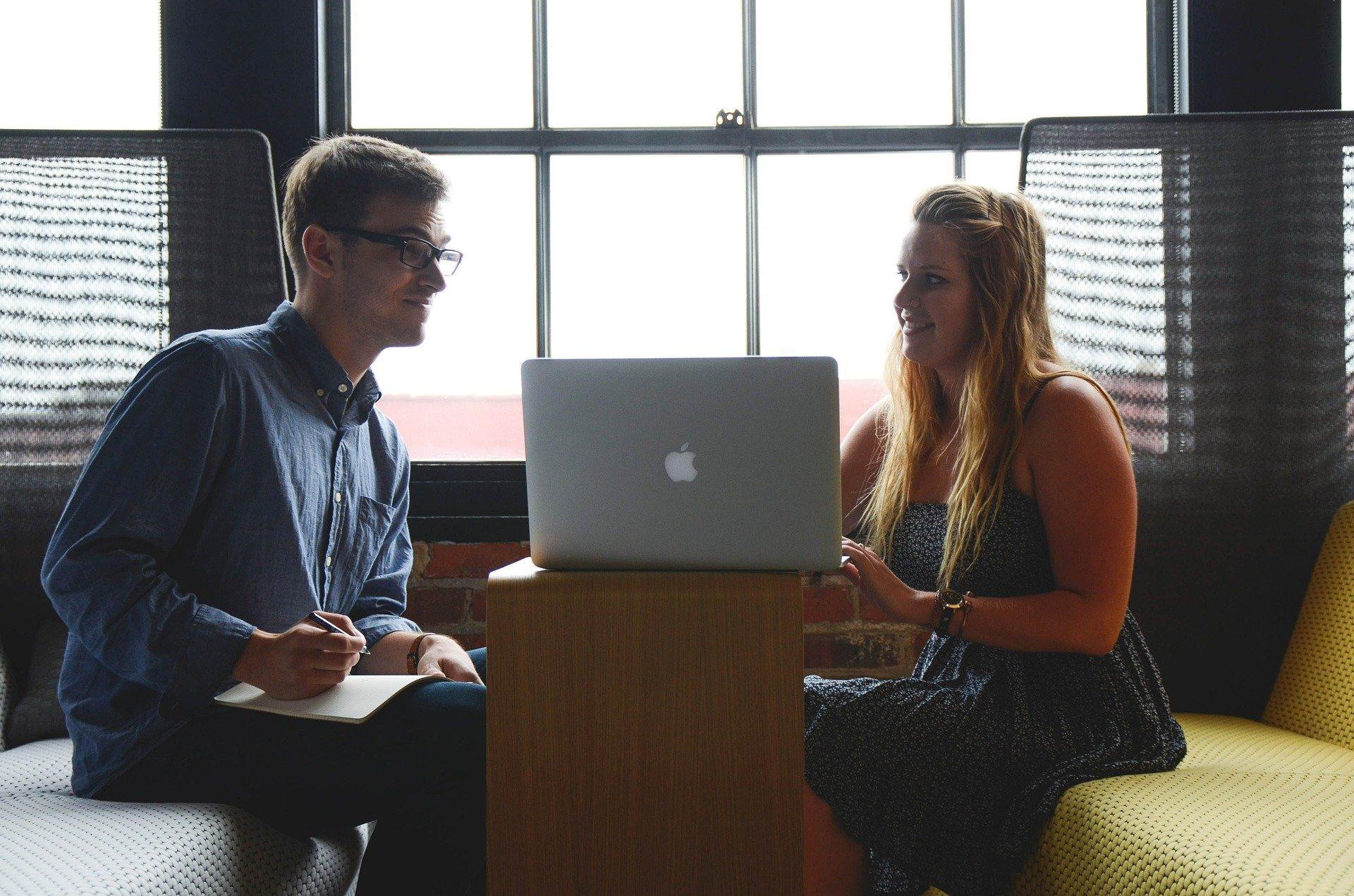 パソコンを置いて会話する男女